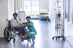 Smiling portrait African American nurse with patient in hospital wheelchair in corridor of specialist care clinic