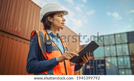 Smiling Portrait of a Beautiful Latin Female Industrial Engineer in White Hard Hat, High-Visibility Vest Working on Tablet Computer. Inspector or Safety Supervisor in Container Terminal. Foto stock ©