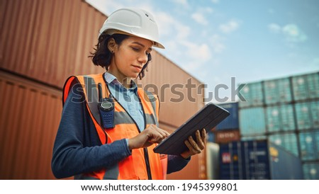 Smiling Portrait of a Beautiful Latin Female Industrial Engineer in White Hard Hat, High-Visibility Vest Working on Tablet Computer. Inspector or Safety Supervisor in Container Terminal. Photo stock ©