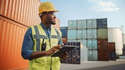 Smiling Portrait of a Handsome African American Black Industrial Engineer in Yellow Hard Hat and Safety Vest Working on Tablet Computer. Foreman or Supervisor in Container Terminal.