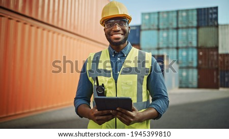 Smiling Portrait of a Handsome African American Black Industrial Engineer in Yellow Hard Hat and Safety Vest Working on Tablet Computer. Foreman or Supervisor in Container Terminal. Photo stock ©