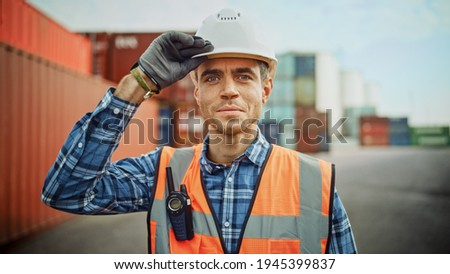 Smiling Portrait of a Handsome Caucasian Industrial Engineer in White Hard Hat, Orange High-Visibility Vest, Checkered Shirt and Work Gloves. Foreman or Supervisor Has a Two-Way Radio Attached. ストックフォト ©