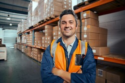 Smiling portrait of a male supervisor standing in warehouse with his arm crossed looking at camera