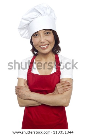 Smiling portrait of confident asian chef. Posing with arms folded