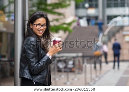 Smiling portrait of young mixed race businesswoman portrait outdoors in Canary Wharf area in London with coffee cup. #296011358