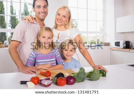 Smiling posing family cutting vegetables together in the kitchen