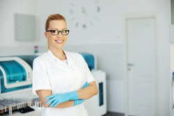 Smiling positive attractive female lab assistant with rubber protective gloves on hands standing in laboratory with arms crossed.
