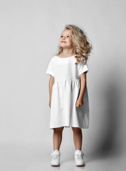 Smiling positive little blonde curly kid girl in white casual dress and sneakers is looking at copy space at upper corner. Stylish comfortable everyday fashion for children concept