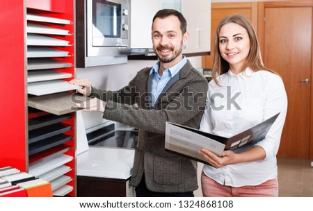 Smiling positive   polite saleswoman helping man to choose materials for kitchen furniture in shop