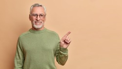 Smiling positive senior man with grey hair and beard points right and shows perfect copy space has brilliant smile white teeth wears optical glasses casual jumper poses against beige background