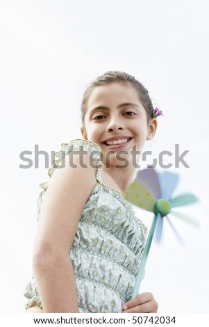 stock photo : Smiling pre-teen girl holding pinwheel, low angle view