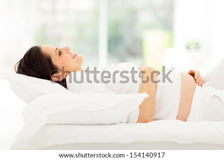 smiling pregnant woman lying on bed