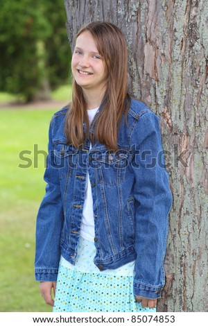 smiling preteen girl dressed in a jean jacket leaning against a tree