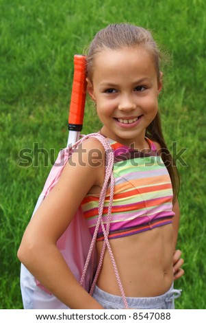 Smiling preteen girl in exercise gear on green grass background ...