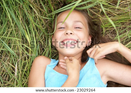 Smiling preteen girl lying on green grass - stock photo