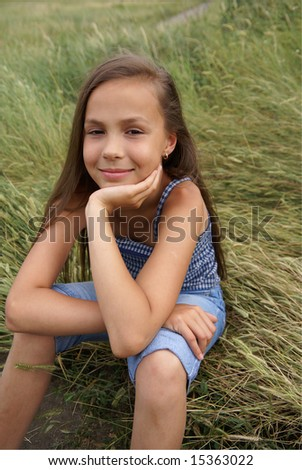 Smiling preteen girl sitting on grass - stock photo
