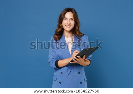 Smiling pretty beautiful attractive young brunette woman 20s wearing basic jacket hold clipboard with papers document writing looking camera isolated on bright blue colour background studio portrait