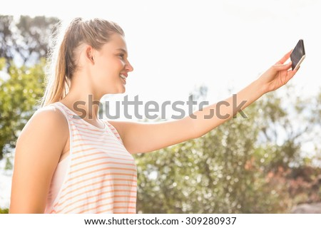 Smiling pretty blonde taking selfies in the nature #309280937