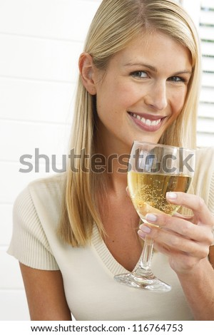 Smiling pretty blonde woman holding a large glass of wine in her hand