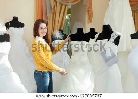 Smiling pretty bride chooses wedding outfit in bridal boutique