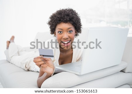 Smiling pretty brunette shopping online using her laptop lying on cosy sofa