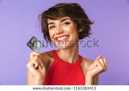 Smiling Pretty brunette woman holding credit card while rejoices and looking at the camera over purple background