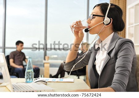 Smiling pretty business woman with headset drinking water in an office environment at foreground. Copyspace - stock photo