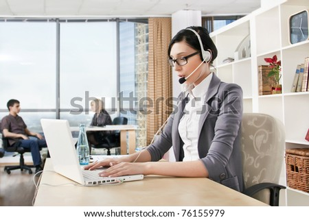 Smiling pretty business woman with headset in an office environment at foreground. Copyspace