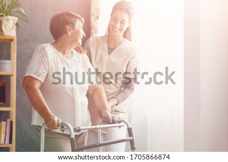Smiling pretty caregiver and old lady with walker at nursing home