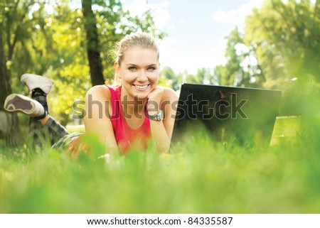 Smiling pretty girl lying down on the green grass, typing laptop computer.
