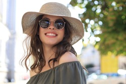 Smiling pretty girl wearing sunglasses and summer hat and looking at camera while walking in city street.