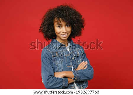 Smiling pretty little african american kid girl 12-13 years old in casual denim jacket holding hands crossed isolated on red color background children studio portrait. Childhood lifestyle concept Stock photo ©