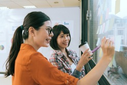 smiling pretty woman designer leader using color pen writing record in memo paper and discussing design idea with staff when they meeting on glass wall.