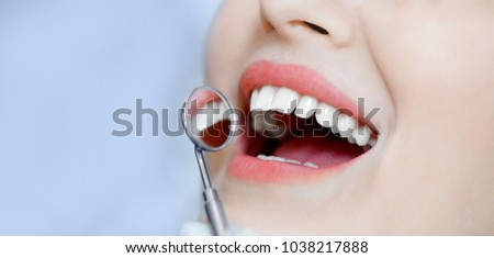 Smiling pretty woman is having her teeth examined by dentist in clinic. Concept health