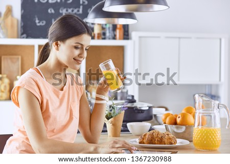 Smiling pretty woman looking at mobile phone and holding glass