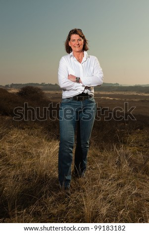Smiling pretty woman middle aged enjoying outdoors. Feeling free standing in grassy dune landscape. Clear sunny spring day with blue sky.