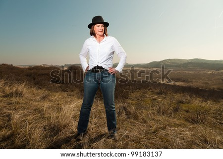 Smiling pretty woman with a hat middle aged enjoying outdoors. Feeling free standing in grassy dune landscape. Clear sunny spring day with blue sky.