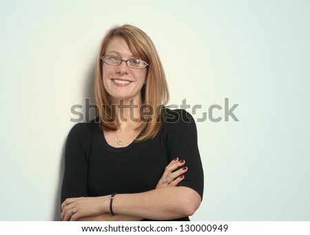 Smiling pretty woman with glasses leaning against wall