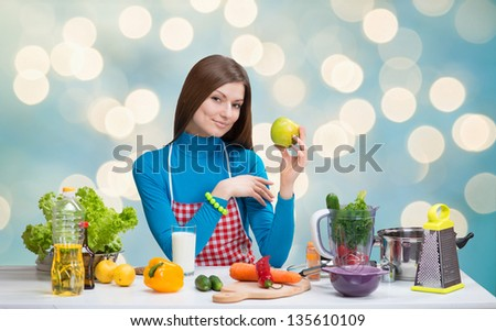 Smiling pretty woman with green apple in the kitchen on abstract blue background