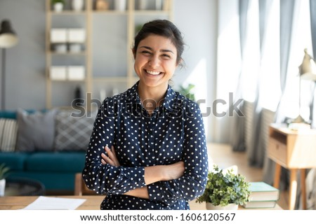 Smiling pretty young adult indian woman looking at camera posing at modern home arms crossed, cheerful happy ethnic girl student self employed lady laughing enjoying distance job education, portrait