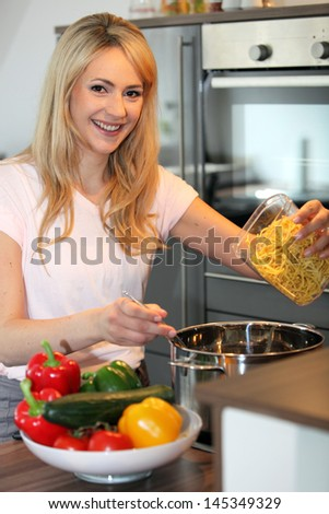 Smiling pretty young blond housewife preparing pasta in the kitchen tipping noodles into a saucepan of boiling water on the stove
