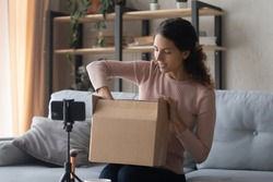 Smiling pretty young female influencer unpacking big cardboard box, sitting in front of mobile phone on stabilizer, sharing internet store shopping experience with followers online or recording video.