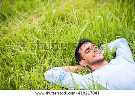 Smiling pretty young man lying, dreaming and relax on the green grass #418217041