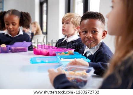 Smiling primary school kids sitting at a table eating their packed lunches together, selective focus