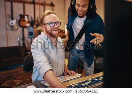Smiling producer and a young African American guitarist talking together over a soundboard during a session in a recording studio #1363064165