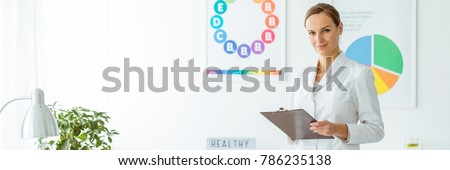 Smiling professional dietician in white uniform against a wall with posters in the office