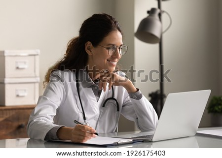 Smiling professional female doctor wearing glasses and uniform taking notes in medical journal, filling documents, patient illness history, looking at laptop screen, student watching webinar