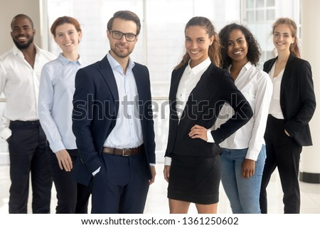 Smiling professional leaders mentors coaches looking at camera with employees business people, happy international staff multi-ethnic team and supervisors posing together in office, group portrait