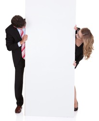 Smiling professional man and woman wearing glasses holding up a blank white sign for your text or advertisement isolated on white