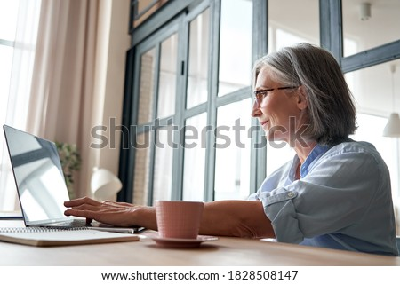 Smiling professional mature middle aged business woman using laptop computer sitting at workplace desk. Happy senior old lady 60s grey-haired businesswoman executive working on pc at home from office.